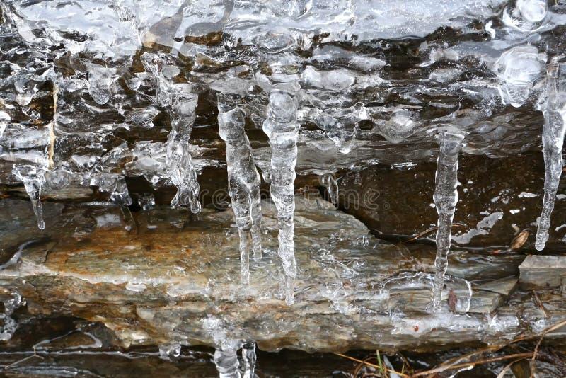 Сосульки таять с падая водой падают в горы стоковые фото