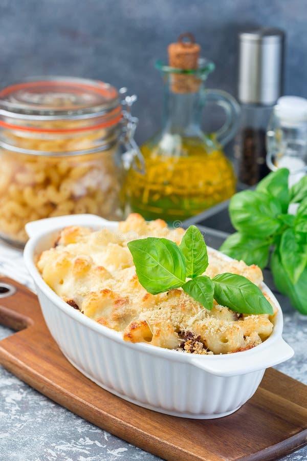 Сотейник макарон с говяжим фаршем, сыром и томатом в печь блюде, вертикальном стоковое изображение
