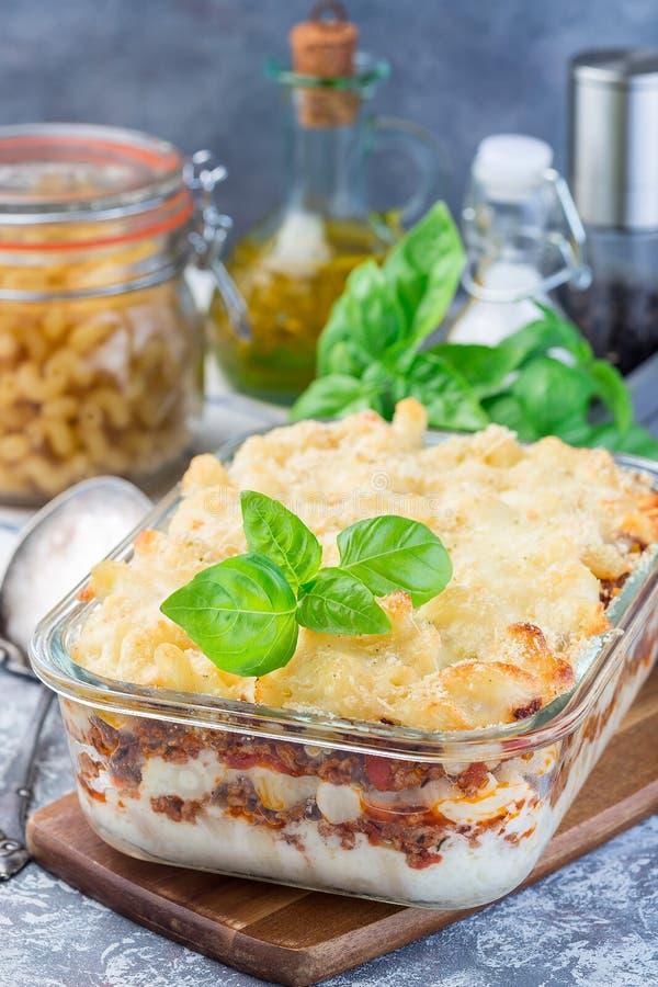 Сотейник макарон с говяжим фаршем, сыром и томатом в стеклянном печь блюде, вертикальном стоковое изображение