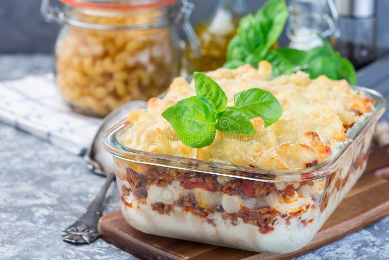 Сотейник макарон с говяжим фаршем, сыром и томатом в стеклянном печь блюде, горизонтальном, космосе экземпляра стоковая фотография rf