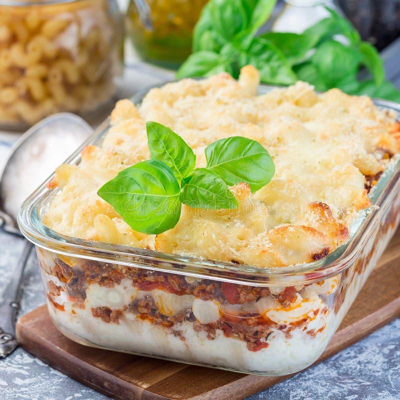 Сотейник макарон с говяжим фаршем, сыром и томатом в стеклянном печь блюде, квадратном формате стоковая фотография