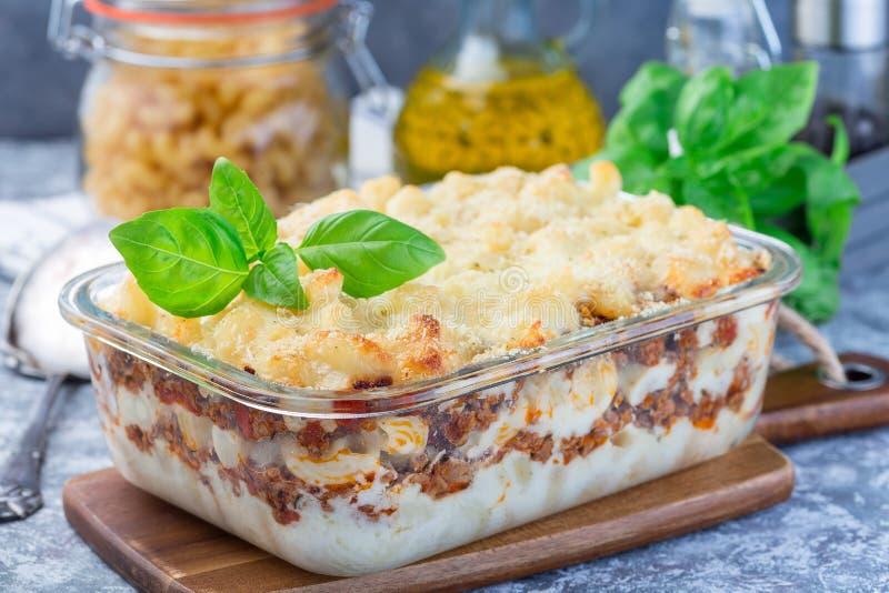 Сотейник макарон с говяжим фаршем, сыром и томатом в стеклянном печь блюде, горизонтальном стоковые фото