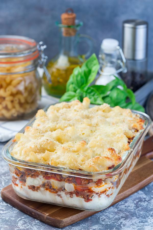 Сотейник макарон с говяжим фаршем, сыром и томатом в стеклянном печь блюде, вертикальном стоковое изображение rf