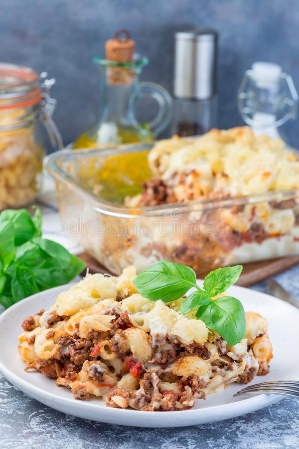 Сотейник макарон с говяжим фаршем, сыром и томатом на плите, вертикали стоковая фотография rf