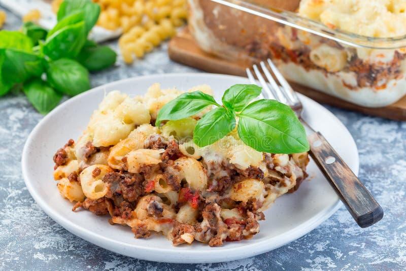 Сотейник макарон с говяжим фаршем, сыром и томатом на плите, горизонтальной, крупным планом стоковое изображение