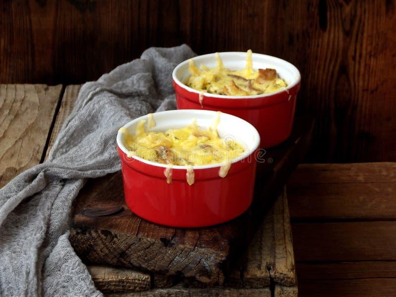 Сотейник от яичек, бекон, высушил томаты и сыр в красном ramekin на коричневой деревянной предпосылке стоковые фотографии rf