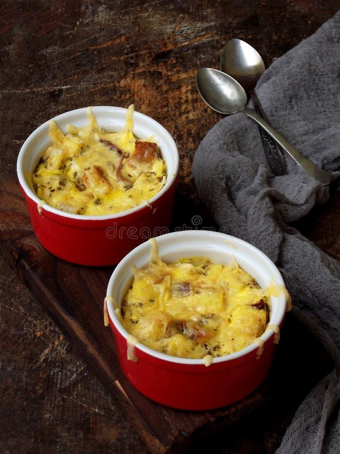 Сотейник от яичек, бекон, высушил томаты и сыр в красном ramekin на деревянной предпосылке стоковое изображение rf