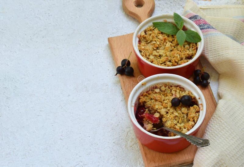 Сотейник плодоовощей или крошит с яблоками и черной смородиной в красном ramekin чашки скопируйте космос Ягода и десерт плодоовощ стоковое фото rf