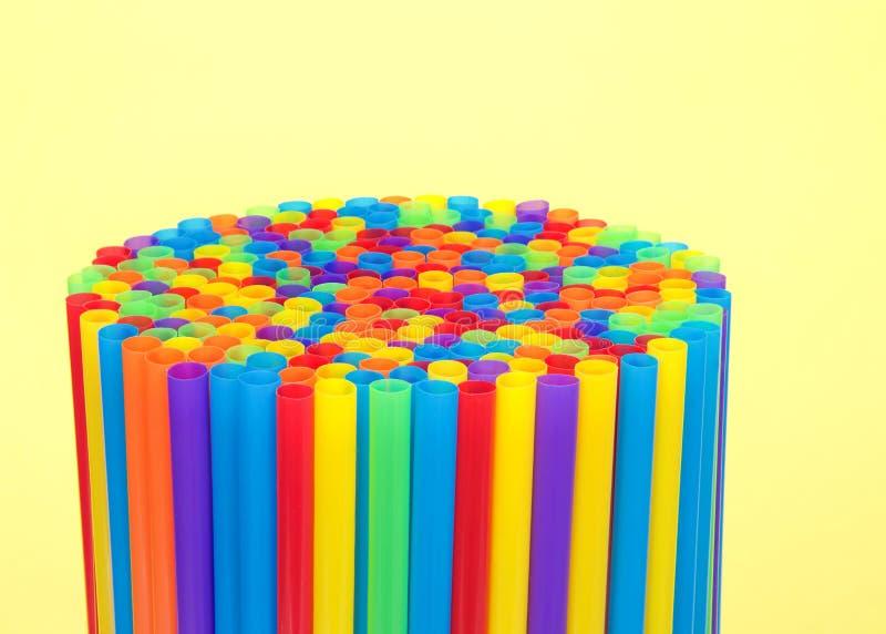 Сотни красочных пластичных солом чистосердечных на желтой предпосылке стоковая фотография