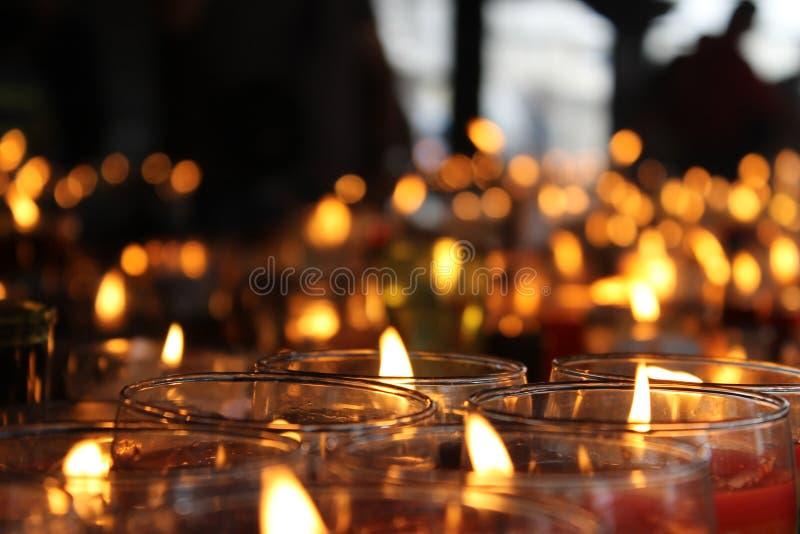 Сотни религиозных свечей с unfocoused предпосылкой стоковые изображения rf