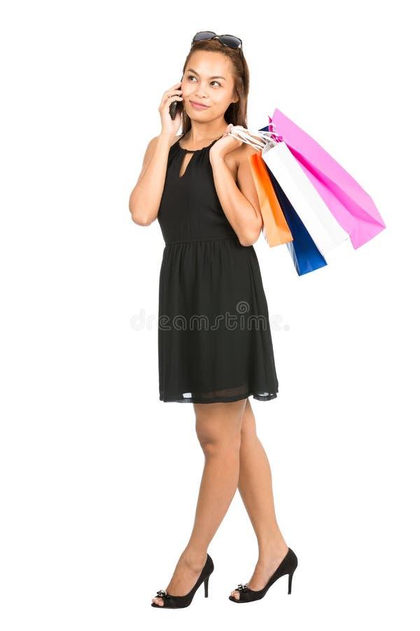 Сотовый телефон азиатского женского покупателя вскользь говоря v стоковое фото