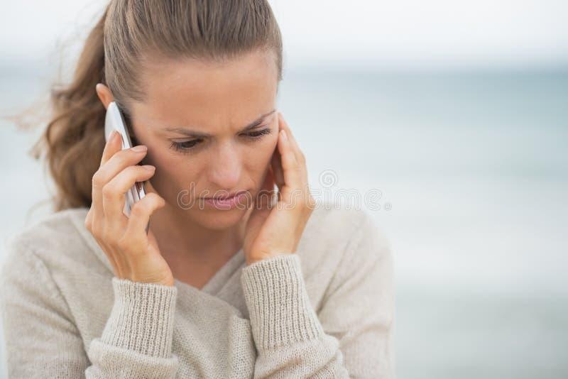 Сотовый телефон Concerned женщины говоря на пляже стоковые изображения rf
