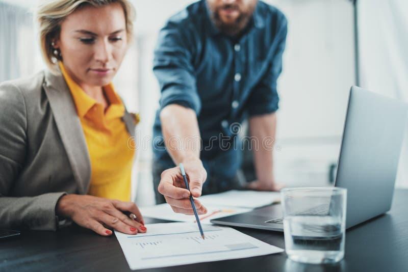 2 сотрудника на работая процессе Молодая женщина работая вместе с коллегой на современном офисе E стоковые фотографии rf