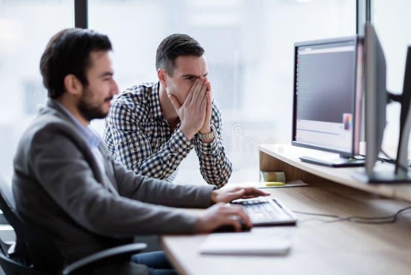 Сотрудники имея проблему с компьютером в офисе стоковая фотография rf