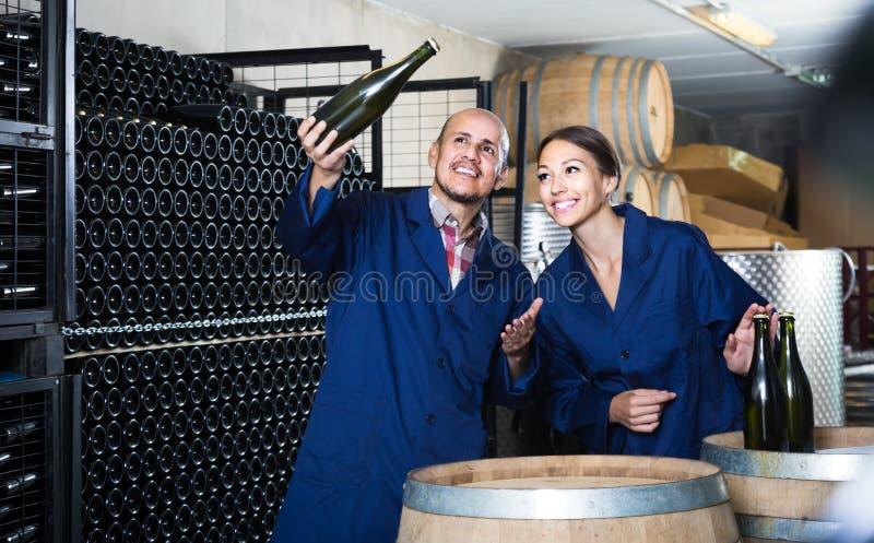 Сотрудники человека и женщин смотря шипучее напитк вино в дежурном бутылки стоковое изображение rf