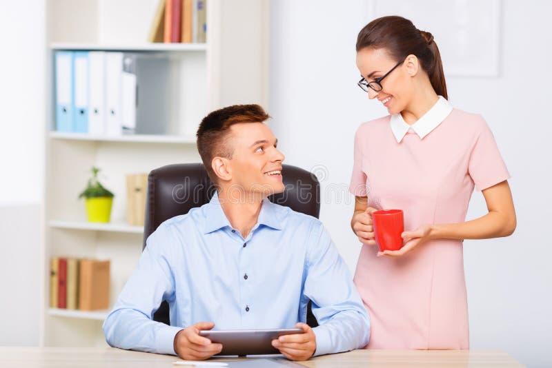 Сотрудник приносит чашку питья к ее партнеру стоковая фотография
