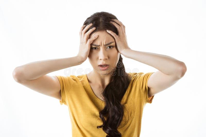 Сотрясенная азиатская девушка с руками на голове стоковое изображение rf