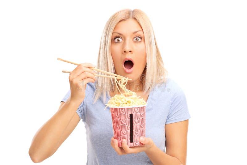 Сотрясенная белокурая женщина есть китайские лапши стоковое фото