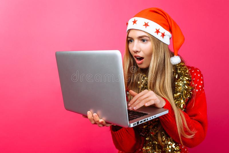 Сотрясенная девушка в красных свитере и шляпе Санта Клауса, с компьтер-книжкой стоковые фото