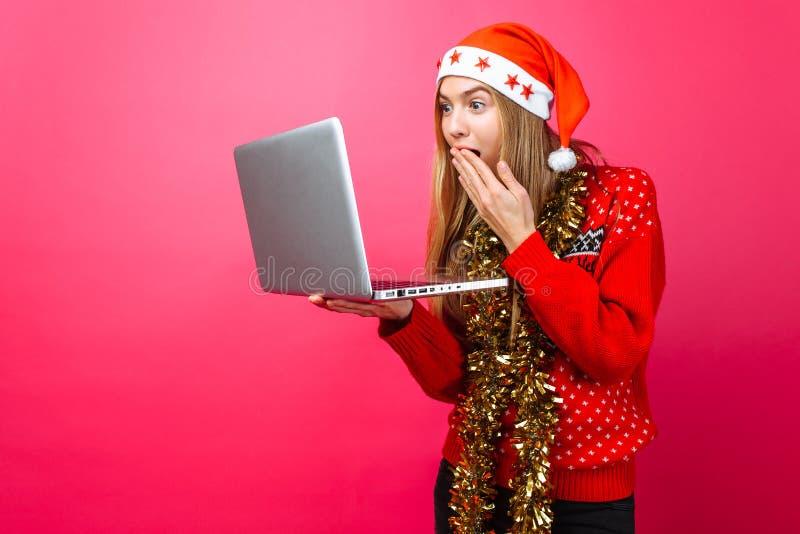 Сотрясенная девушка в красных свитере и шляпе Санта Клауса, с компьтер-книжкой стоковое фото rf