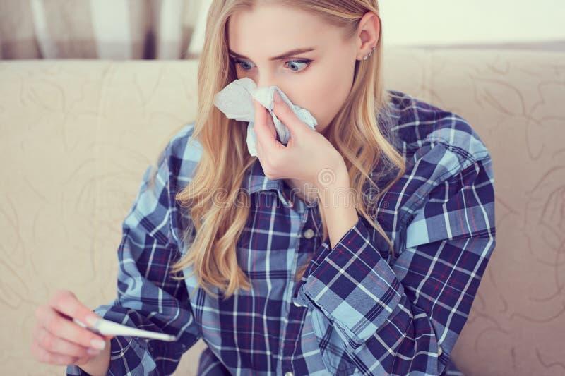 Сотрясенная девушка смотря на термометре пока сидящ на софе дома стоковые изображения