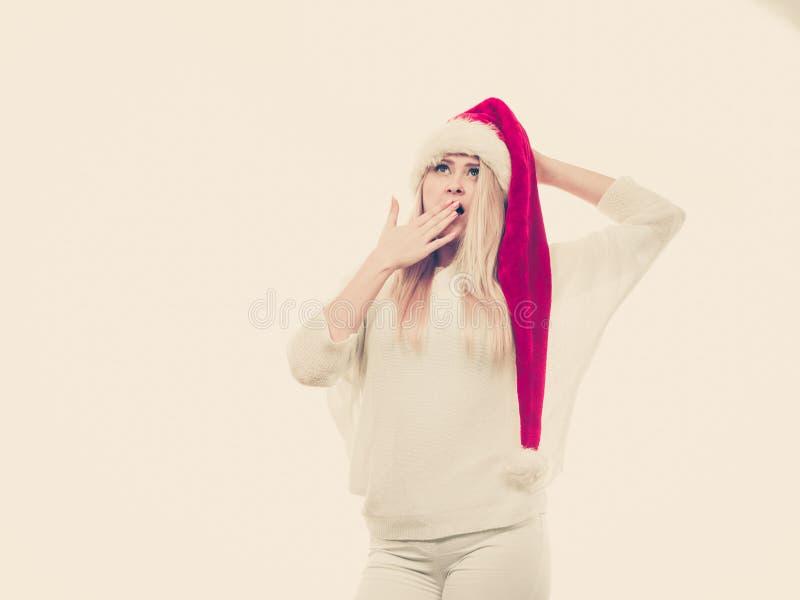Сотрясенная женщина нося шляпу хелпера Санта Клауса стоковое фото rf