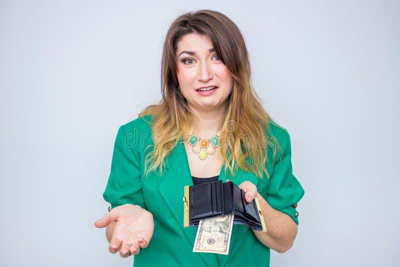Сотрясенная коммерсантка нося в зеленой куртке без денег, женщина с бумажником без денег стоковая фотография rf