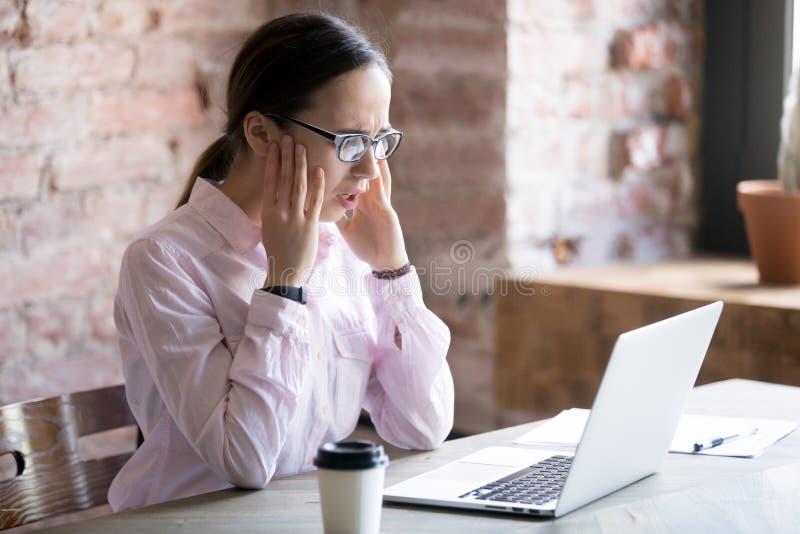 Сотрясенная коммерсантка смотря экран ноутбука со страхом стоковая фотография rf