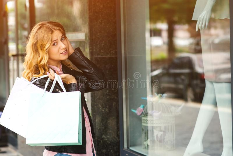 Сотрясенная молодая дама с хозяйственными сумками, смотря через окно магазина Большие сезонные продажи Магазин моды женщин Стильн стоковое изображение rf
