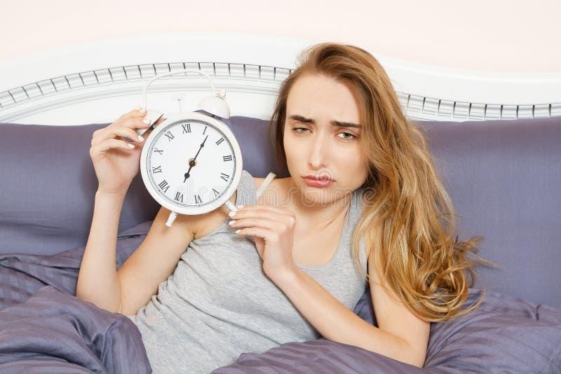 Сотрясенная молодая женщина просыпая вверх с сигналом тревоги, overslept работой, плохой инсомнией сна Часы владением девушки леж стоковые изображения