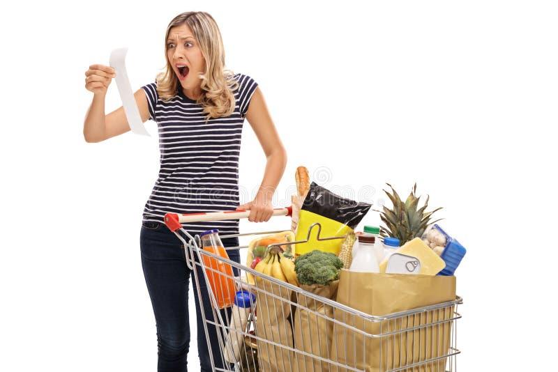 Сотрясенная молодая женщина смотря получение магазина стоковые изображения