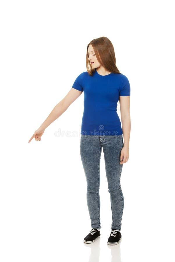 Сотрясенная молодая женщина указывая вниз стоковое фото rf