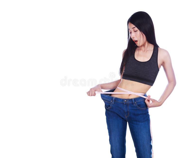 Сотрясенная тонкая женщина фитнеса в старых джинсах и измеряя ленте позже стоковая фотография