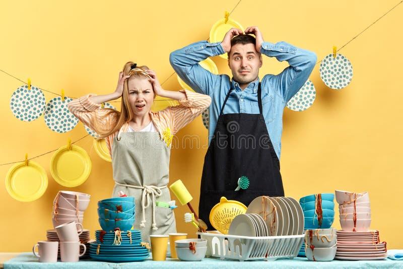 Сотрясенные пары с руками на их головах смотря камеру стоковые изображения