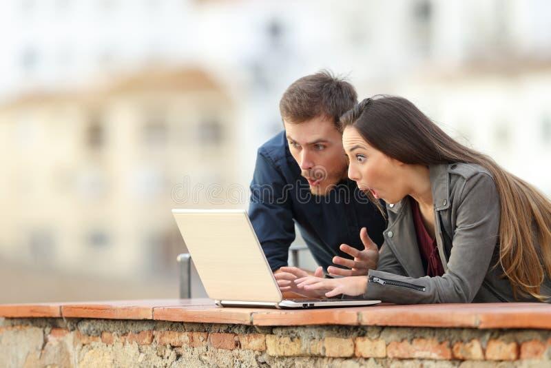 Сотрясенные средства массовой информации пар наблюдая на ноутбуке стоковая фотография