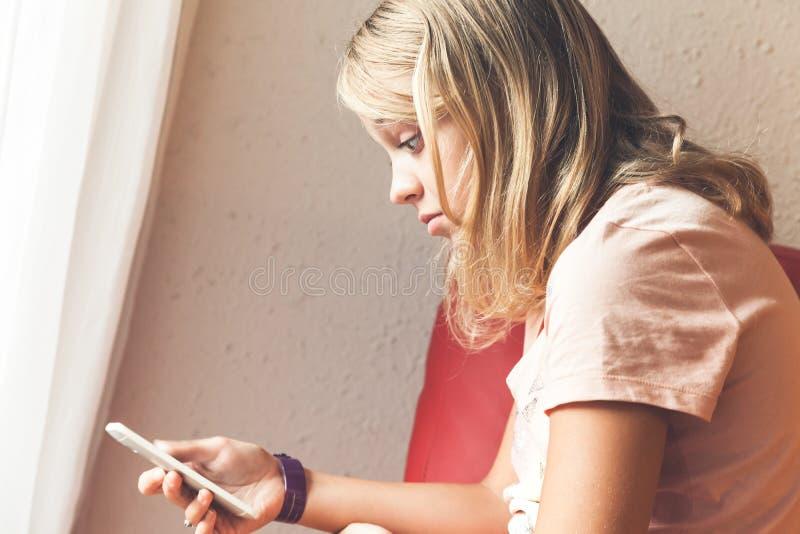 Сотрясенный белокурый девочка-подросток с smartphone стоковые изображения rf