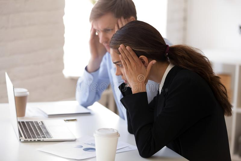 Сотрясенный бизнесмен и коммерсантка получая плохую новость стоковые фотографии rf