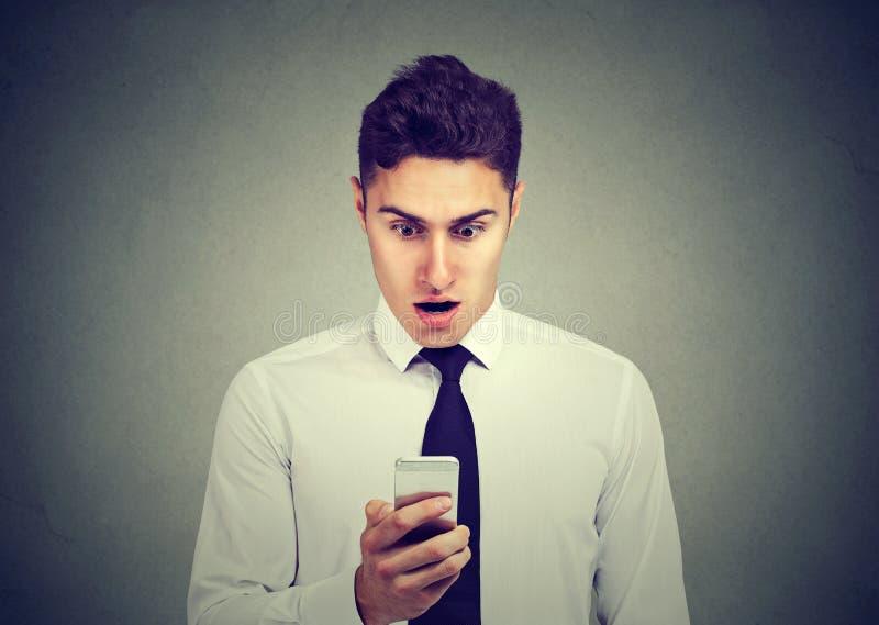 Сотрясенный бизнесмен проверяя его мобильный телефон стоковая фотография rf