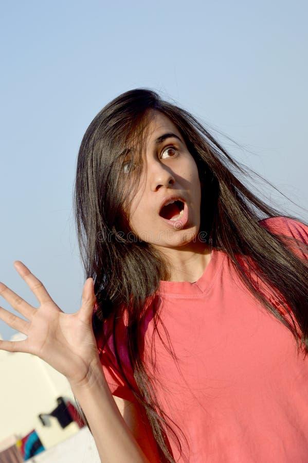 Сотрясенный девочка-подросток стоя в ее крыше дома стоковая фотография