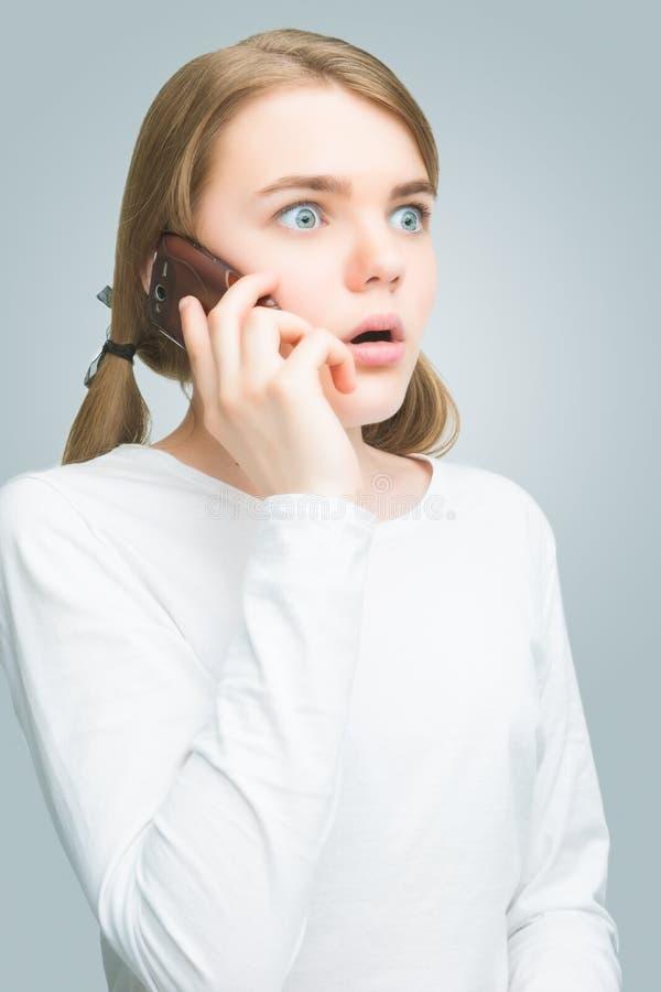 Сотрясенный девочка-подросток говоря на мобильном телефоне. изолированный стоковые фотографии rf