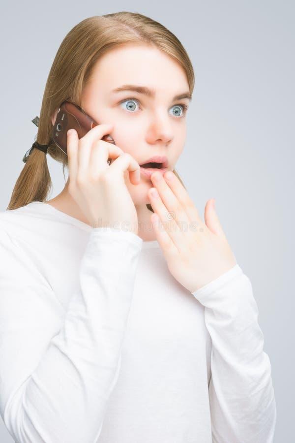 Сотрясенный девочка-подросток говоря на мобильном телефоне. изолированный стоковое фото