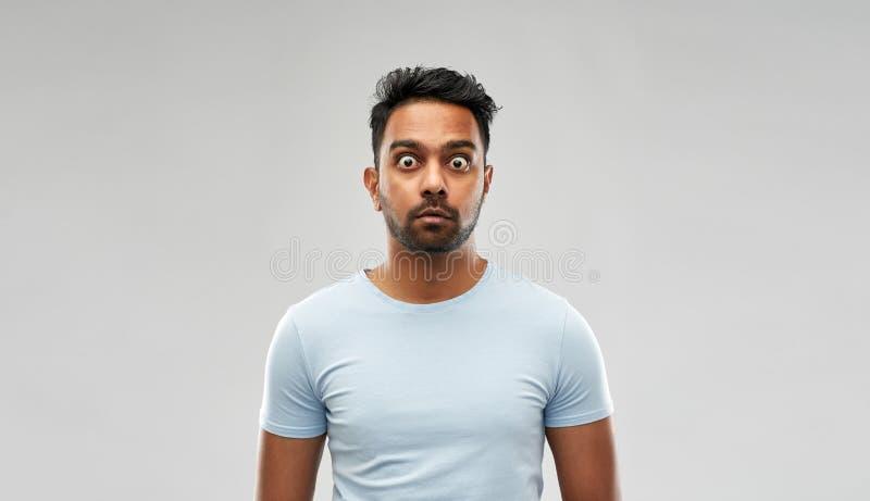 Сотрясенный или вспугнутый человек над серой предпосылкой стоковое изображение rf