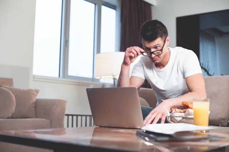 Сотрясенный парень работая на компьютере дома стоковое фото rf