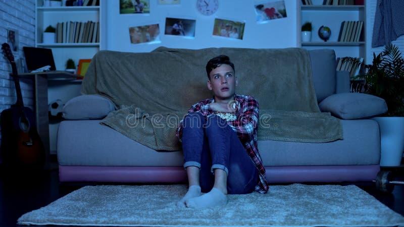 Сотрясенный подросток смотря фильмы ужасов по телевизору поздно вечером, эмоции стоковые изображения
