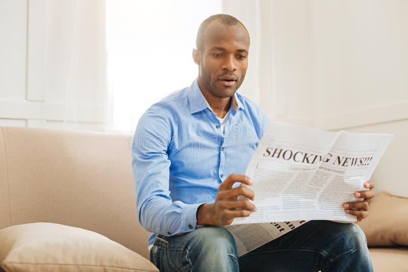 Сотрясенный человек читая газету стоковое изображение