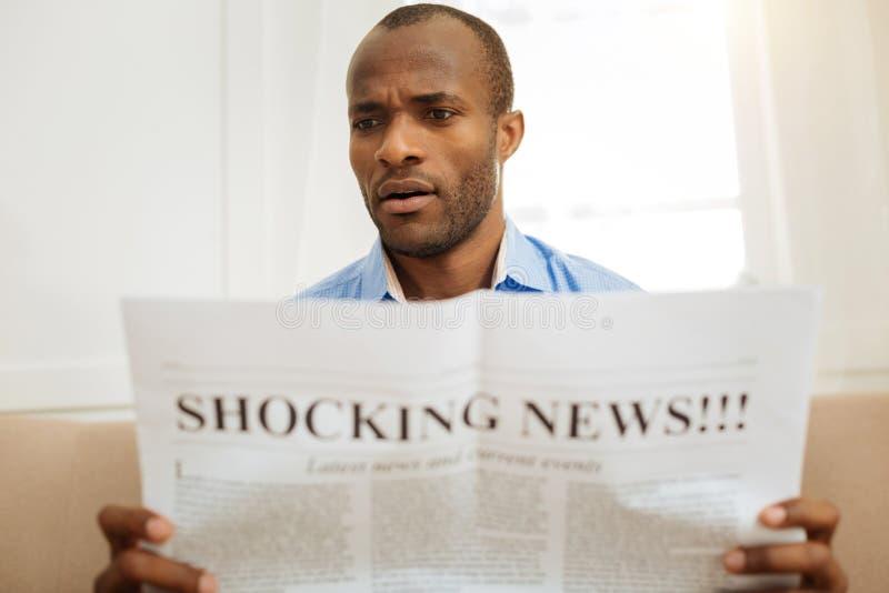 Сотрясенный человек читая газету стоковые фото