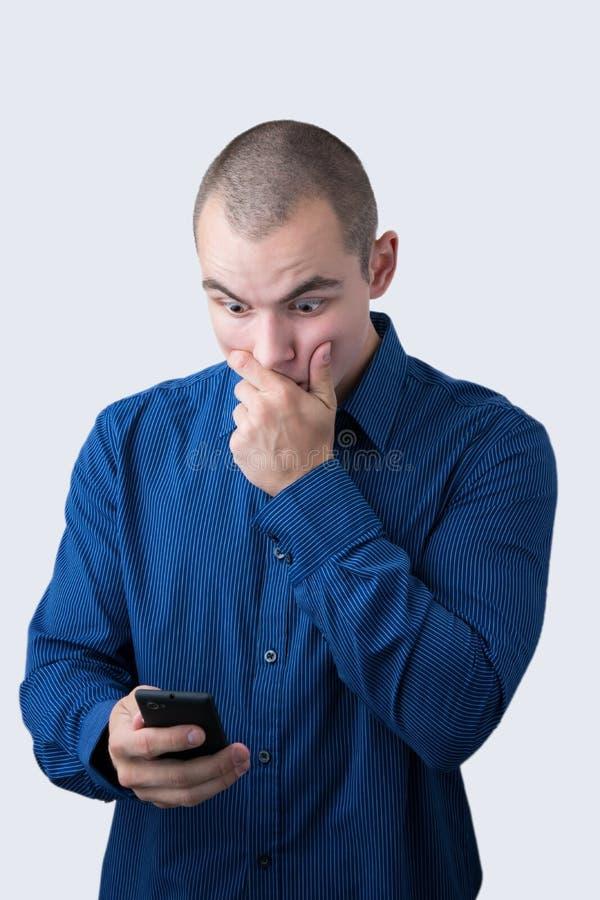 Сотрясенный человек просматривая его smartphone стоковая фотография rf