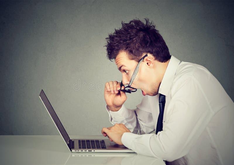 Сотрясенный человек смотря портативный компьютер изумил с открытым ртом стоковые фотографии rf