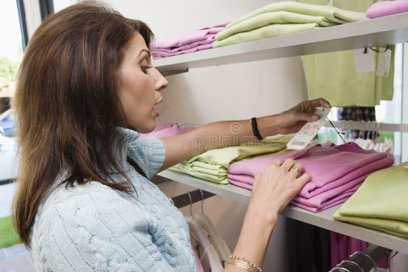 Сотрястенная женщина смотря цену в магазине одежды стоковая фотография rf
