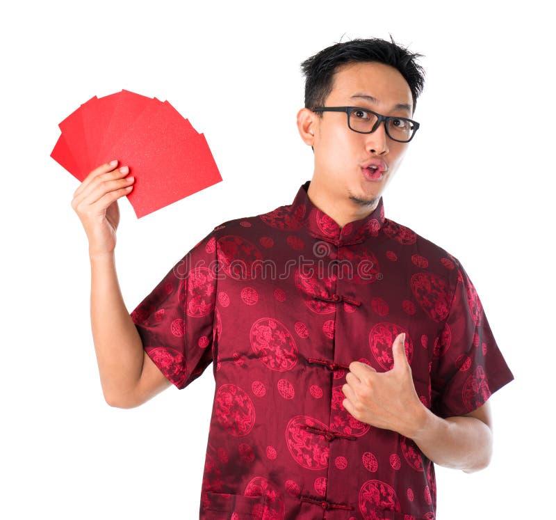 Сотрястенный азиатский китайский человек держа много красных пакетов стоковое изображение